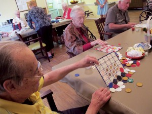Residents play a board game at Cypress Creek in one of the neighborhoods. Photo Lia Martin