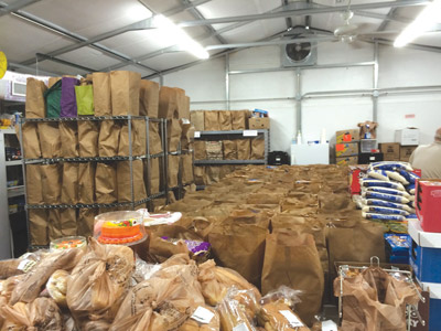 The Community Cupboard at Calvary Lutheran Church helps hundreds stave off hunger with its weekly food baskets. Above, some of the food the church gave out just before Thanksgiving last year.