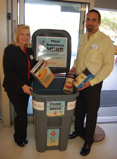 Winn-Dixie in Sun City Center has a food container near the exit door for donations. Sharon Wolf, service lead, and John Custode, manager of the store, deposit items to kick off the campaign. Chere Simmons photo.