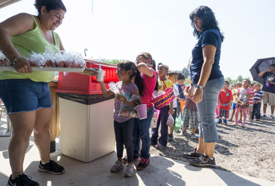 Strawberry Market manager Zenaida Silva hands out fresh strawberry milkshakes and freshly baked cookies to children from Wimauma Elementary School on Friday.