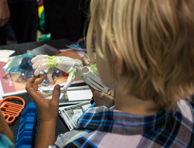 A child looks at a 3D printed prosthetic hand during MakerCon, a convention of inventors and innovators held in Tampa on April 18. The hand was among several on display at the booth of e-NABLE and the local organization Handling the Future.  Mitch Traphagen photos.