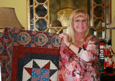 "Cindy Falck of Apollo Beach shows off a quilt created by the ""Quilts of Valor"" neighborhood sewing group.  Lisa Stark photos."