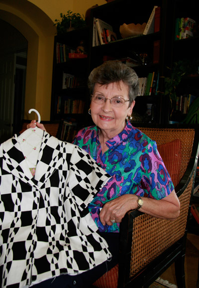 "Delores Lines displays two blouses she has made — including the one she's wearing. Below, colorful pillowcases created for charity by the ASG chapter ""Sewing Sisters."""