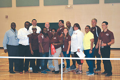 Park staff and visiting dignitaries pose behind the pickleball net in the new gym.