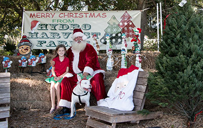 At Hydro Harvest, Santa poses with 9-year-old Rory and Bubba the dog.
