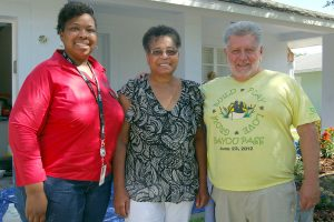LOIS KINDLE PHOTOS Standing outside her newly painted home in Summerview Oaks, Hazel Jackson, center, is surrounded by Latasha Price of the USDA Rural Development Agency and Earl Pfeiffer, executive director of the Florida Home Partnership.