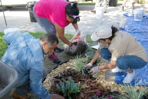 Manuel Soto, owner of Manny's Landscaping in Riverview, Vanessa Josey and Mary Bernardino work on a garden bed in Hazel Jackson's front yard. Volunteers made the beds, edged and filled them with rock and mulch, and then installed colorful flowers and other plants like these. Soto donated materials and labor.