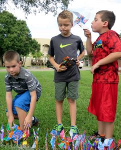 Justin Anglin, left, plants the pinwheel he made in art class for Pinwheels for Peace, while fellow Apollo Beach Elementary School students Bruce Dehaan and Eric Schwartz wait their turns.
