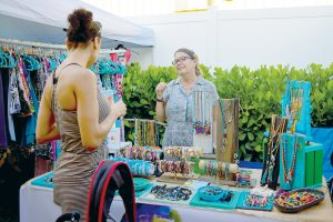 Rexy Sharp, owner of The Babe Cave, talks with a customer about her oil-infused jewelry.
