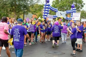 Volunteers and friends of participants in the 2016 South Shore Walk to End Alzheimer's cheer them on across the finish of their two-mile trek.