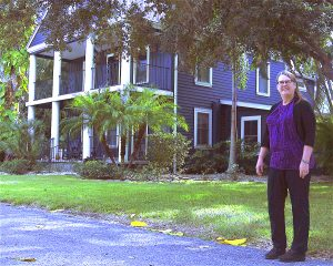 CARL MARIO NUDI PHOTOS Cathy Slusser stands in front of the home on 29th Street Northwest in Bradenton where the three main women characters of her novels lived.