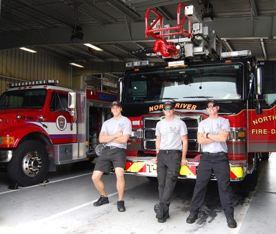 Engineer and firefighters in front of a fire truck