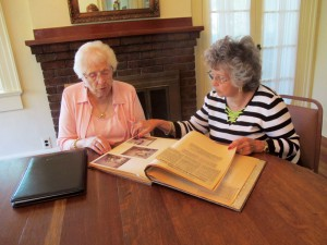 From left, Wilma Wood and Phyllis Elsberry look at some older scrapbooks compiled of Ruskin Woman's Club members and events.  Photo Lia Martin