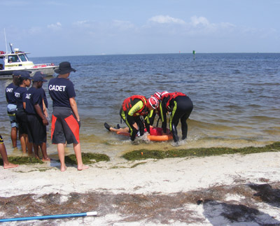 """The """"victim"""" is brought to shore on a special board, with care taken that his neck and back are not further damaged. Penny Fletcher photos"""