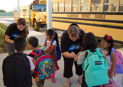 School workers put arm bands on students as they exit the buses. Each was also given a high five and a hearty welcome to school.
