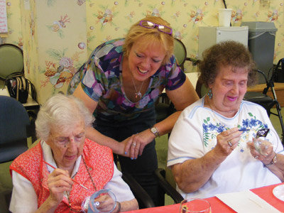 Brenda shows 12 women at SunTowers Retirement Community in Sun City Center how to paint intricate designs either freehand or using stencils on various sizes and shapes of glassware Sept. 6. Penny Fletcher photo.
