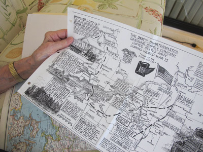 Murray Cashdollar holds a hand-drawn map that was created after World War II, with the help of a serviceman's son and notes supplied by Cashdollar and others. It shows a timeline of the war experienced by the 3937th Quartermaster Gasoline Supply Company, U.S. Army. Lia Martin photo.