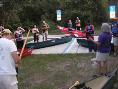 Daniel Allen helps canoers into their boats and gives the canoes a shove. Penny Fletcher photo.