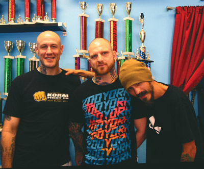 """Standing in front of the """"Wall of Trophies"""" displaying awards from national and international competitions are, from left, Mike Parsons, Kurtis Todd and Matt Lang of Mike Parsons Ink. Not pictured, Derek Raulerson."""