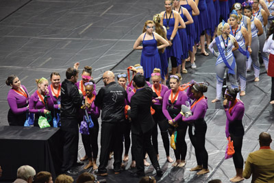 Staff members place silver medals on the girls during the awards ceremony.