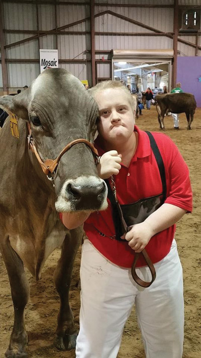 Joshua Holmes, who started showing cows in 2002, was the inspiration for the Sassy Cows program. Throughout his seven years of showing, he had a Sassy 1, Sassy 2, Sassy Cinnamon, and his last heifer, Sassy Jo. At left, he shows Sassy Jo (now 7 years old), at the 2015 Florida State Fair.
