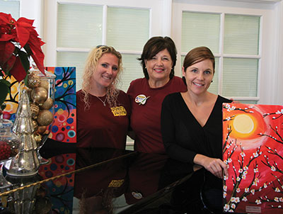 Pinot's Palette franchise owner Beverly Walker, center, spreads holiday cheer with two of her art instructors, Jessie Snyder, left, and Kelly Lorenz.
