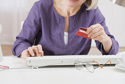 senior-woman-with-credit-card-on-computer