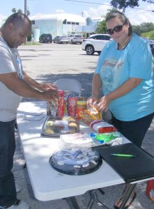 Pastor Freddie Roberts, Minerva Garcia and Madeline Hughes (not pictured) work every Thursday dispensing food to the homeless in Ruskin. During the week Garcia uses her couponing skills to get more bang for the buck.