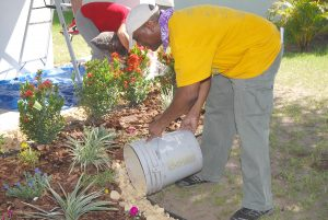Project supervisor Joey Henderson, community development manager for the Florida Home Partnership, pitches in by adding a border of rock to Hazel Jackson's flower bed.
