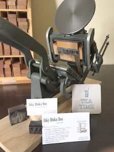 A Kelsey printing press sits atop a desk in the home office of Kurt Carr. On display are some business cards and ephemera Carr printed.