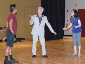 Alan Tulin, middle, playing the character of play director Julian Marsh, gives instructions to his stage manager, played by Angelo Jasa, while Sarah Cassidy, as Peggy Sawyer, reacts.