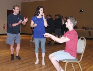 """Brian Chunn, as Billy Lawler, serenades Sarah Cassidy, who portrays Peggy Sawyer, with the """"musical accompaniment"""" of actor Jack Kaiser during rehearsal of 42nd Street."""