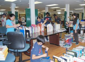 Volunteer students with the Action Team school organization help get the Manatee School for the Arts library in order before school starts.