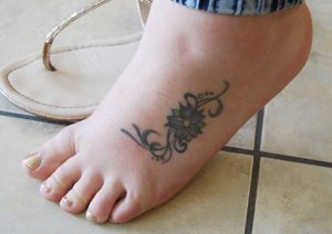 Megan Ryan got her first tattoo, a flower on her foot, when she was 15 years old.