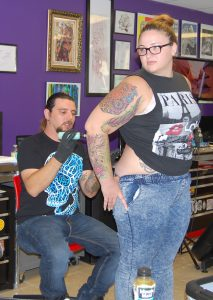 Tattoo artist Manny Lopez prepares to do a cover-up tattoo on Megan Ryan's back.