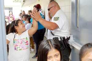 LOIS KINDLE PHOTOS Eight-year-old Rubi Arreola gives HCSO Deputy Ernie Foster a high five as she re-enters the Wimauma Boys & Girls Club after a group photo during the Aug. 12 backpack giveaway.