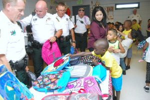 Tyree Walker, foreground, and Jeremiah Camargo, both 6, lead other school-age children from low-income families in the Wimauma area to pick out a free backpack filled with school supplies from Hillsborough County Sheriff's Office deputies from Dist. IV.