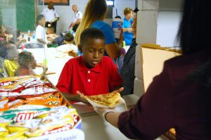 Lavonte Carrie, 9, gets a piece of pizza as part of his after-school snack at the Wimauma Boys & Girls Club Aug. 12.