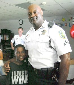 Master Deputy Harold Hoskins poses for a picture with a delighted Harece Carrie, 7, at the HCSO's recent backpack giveaway at the Wimauma Boys & Girls Club.