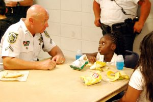 Deputy Don Hess visits with 6-year-old Taylor Burton at the Wimauma Boys & Girls Club, during a special event Aug. 12, where each child received a free backpack from the Hillsborough County Sheriff's Office Dist. IV Command.