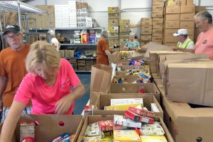 PHOTOS BY LOIS KINDLE Volunteers at Calvary Lutheran Church's Community Cupboard fill bags of food during the waning hours of the cupboard's weekly, free distribution to more than 400 families who live in South Shore. The pantry is open Tuesdays from 9 to 11 a.m.