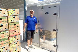 Jim Wise, Community Cupboard operations manager, stands beside the new 260-square-foot walk-in cooler/freezer purchased with the help of a $20,000 grant from the Community Foundation of Tampa Bay. The unit now enables the food pantry to add a meat item and fresh produce to the cans or boxes of food it gives away each week to at least 1,900 people.