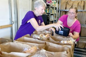 Volunteers Nan Ryan and Michelle Golly check and finalize food bags waiting for people to pick them up at Community Cupboard in Ruskin.