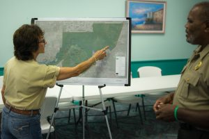 Cathy Moore of Friends of the Little Manatee River State Park and Park Manager Joe Howard discuss proposed changes to the park from a large satellite photo provided at the public hearing last week.
