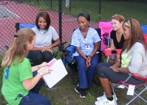 "Paula Knight, left front, volunteers as the ""business manager"" for the club, keeping records, listing needs, and (like she's doing here, taking in the hopes and ideas of parents. Parents, from left, are: Jessica Cuello, 'team nurse' Crystal Davis, Nicole Smith and Oquicha Mattox."
