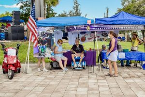 ANDREA SHAY PHOTOS Next to the music stage, Wheels 4 Purple Hearts offers information and raffle opportunities in order to raise money for the custom wheelchairs they give to veterans in need who've been injured while serving.