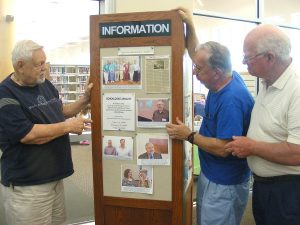 Jack Fischer, Ed Frank and Don Churchill of the South Bay Genealogical Society update their events board in the Genealogical Society's room at the SouthShore Regional Library.