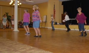 Enrichment Center members and guests learn country line dancing on the dance floor of the Turner Ballroom in the Renaissance on 9th.