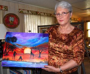 Mara Trumbo holds one of a series of paintings she did influenced by living in Africa.