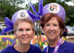 Lori Gaber, of Sun City Center, and Melanie Hawkins, of St. Petersburg, wearing purple hats bearing the photos of those they walked for, pause for a photo during the 2016 South Shore Walk to End Alzheimer's in Sun City Center.